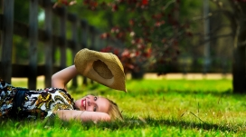躺在绿色草坪上拿帽子的欧女