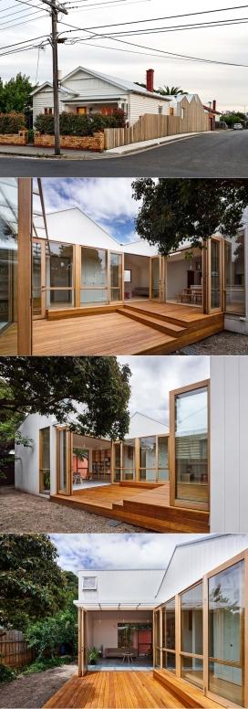Profile House-坐落在澳大利亚墨尔本工业区,木墙上有三个小建筑物,周围有砖瓦楞铁仓库
