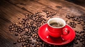 条纹木板上的咖啡豆与热气腾腾的红色咖啡杯