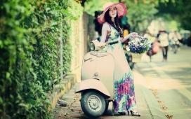 女性摩托车旁手提花篮的亚洲女孩