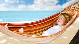 躺在沙滩吊床摇篮中的金发女宝宝