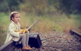坐在废弃铁轨上带行李箱的国外小女孩