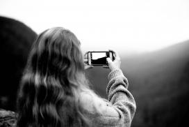 用iPhone拍照的卷发美女