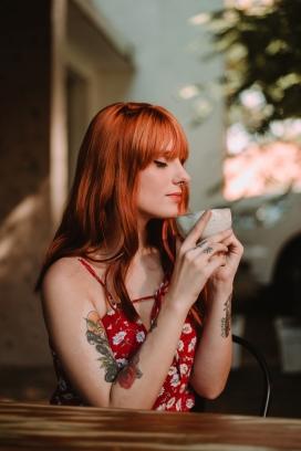 红发纹身品咖啡的女子