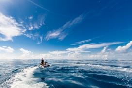 蓝色海洋中骑摩托艇的情侣