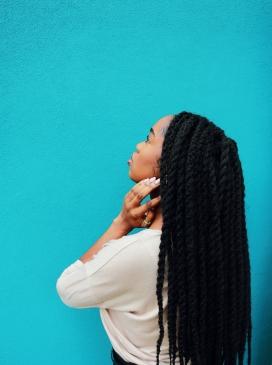 蓝色墙前的长黑发非洲女郎
