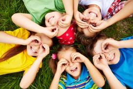 躺在草坪上用手做眼镜的五个小朋友