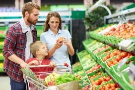 一家人推购物车在超市购买西红柿