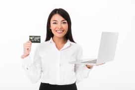 手拿笔记本电脑与银行卡的女子