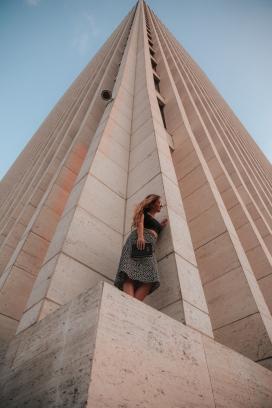 仰拍高楼建筑下躲猫猫的女郎
